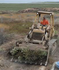 Om cu buldozer pe teren viran