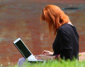 Femeie scriind la laptop